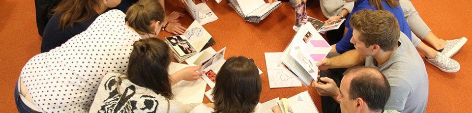Ein Gruppe Studierender sitzt im Kreis auf dem Boden. In den Händen halten sie Zines