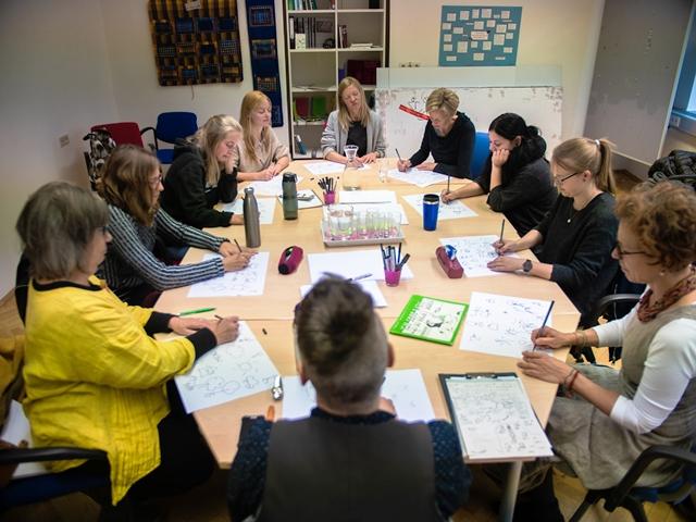 Eine Gruppe Studierender sitzt um einen Tisch und zeichnet