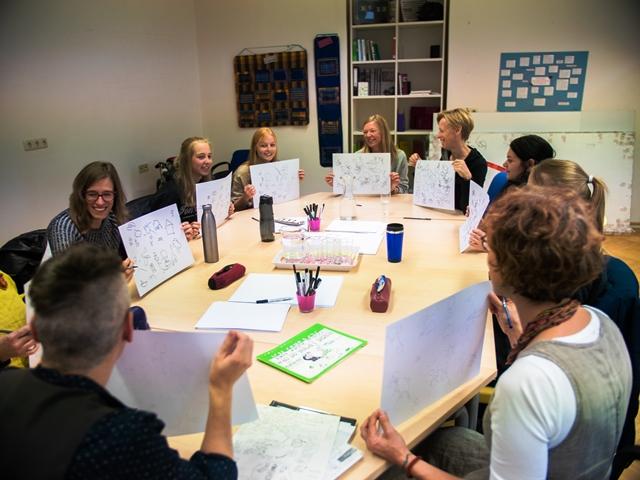 Eine Gruppe Studierender sitzt um einen Tisch und zeigt die eigenen Zeichnungen her.