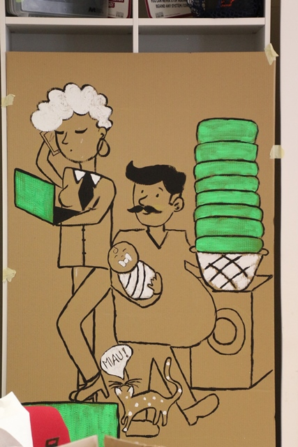 Die Pappfiguren zeigen eine Frau mit Karrieresymbolen Handy und Laptop und einen Mann, der sich um Kind und Haushalt kümmert