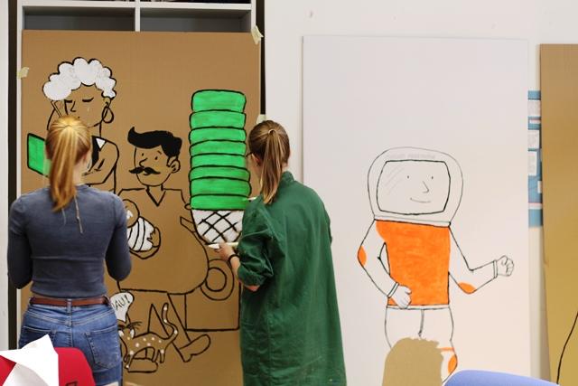 2 Studentinnen arbeiten an einer lebensgroßen Pappfigur