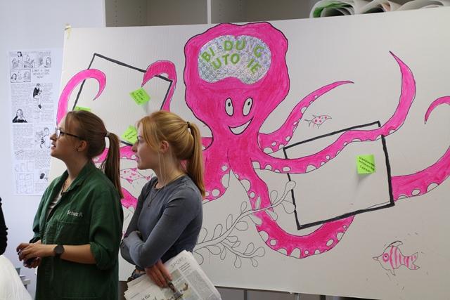 2 Studentinnen stehen vor einem Kraken aus Karton der die Aufschrift Bildungsutopie trägt