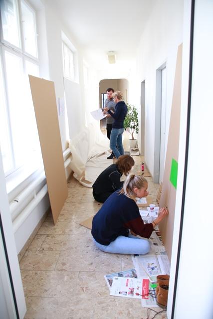 Vier Personen arbeiten an großen Pappfiguren