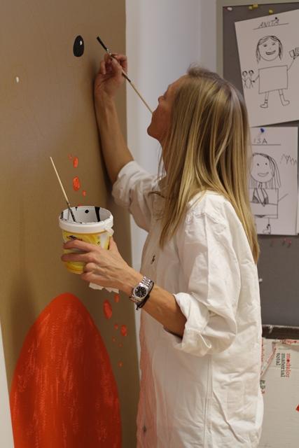 Eine Studentin malt an einer lebensgroßen Figur aus Karton