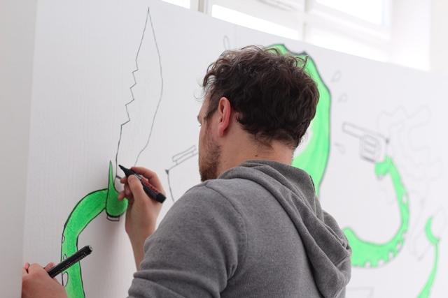 Ein Student zeichnet an einer großen Krake aus Karton.