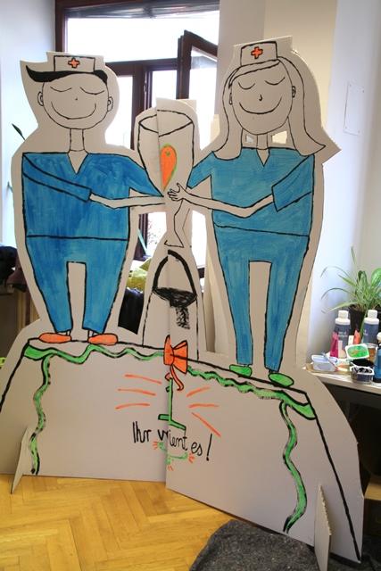 Das Bild zeigt 2 Pappfiguren, die auf einem Podest stehen und einen Pokal halten. Darunter steht ihr verdient es