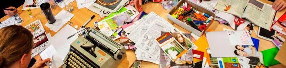 Das Bild zeigt einen Tisch, der mit Zeitschriften übersät ist, außerdem eine Schreibmaschine und eine Person, die etwas ausschneidet