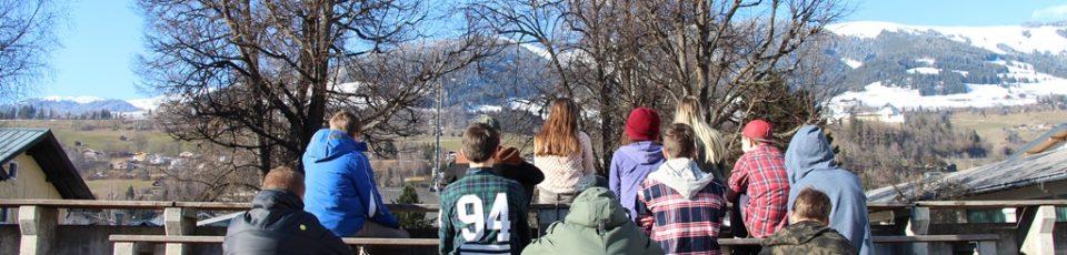 Das Bild zeigt eine Gruppe Jugendlicher von hinten auf Bänken sitzend, die in Richtung Berge schauen