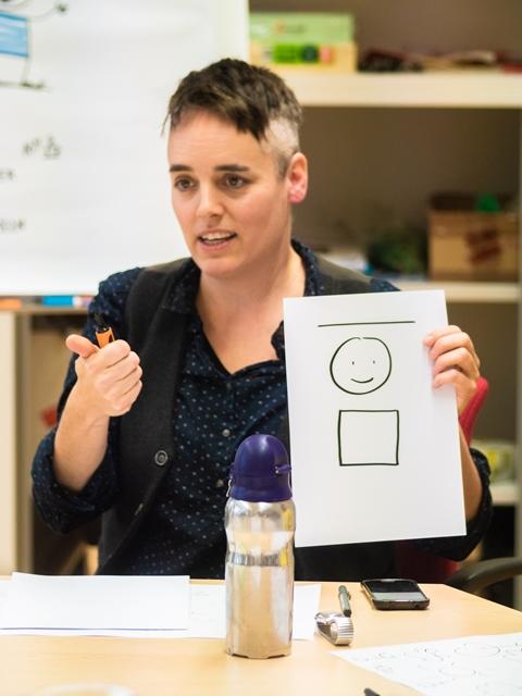 Ka Schmitz erklärt etwas und hält eine Zeichnung mit einem einfachen Strichmännchen in der Hand.