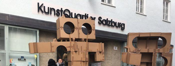 Das Bild zeigt die Köpfe zweier Kartonfiguren vor dem Eingang des Kunstquartier salzburg