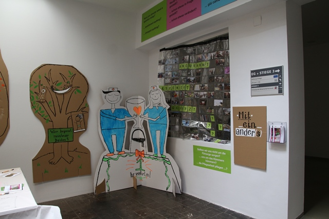 Ausstellung miteinanders. in einer ecke stehen große ausgeschnittene pappfiguren, die zwischen sich einen pokal halten. daneben ein baum auf pappkarton