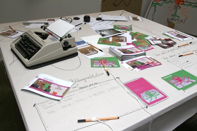 ein tisch mit einer schreibmaschine und flyern. beschriftungen und stiften