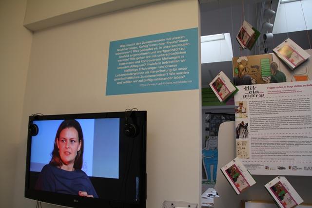Ausschnitt aus der Ausstellung. ein Monitor mit einem frauengesicht, darüber ein blaues plakat mit unleserlicher schrift. daneben ein aufgehängtes plakat ebenfalls unleserlich