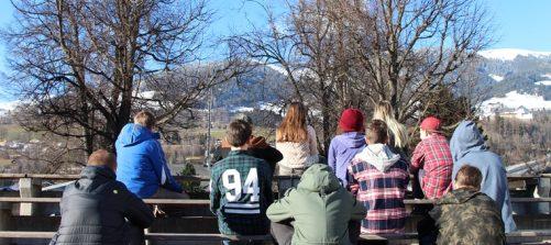 eine gruppe jugendlicher sitzt auf einer tribüne im hintergrund berge