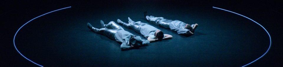 auszug aus einer performance: 3 menschen liefen auf dem boden innerhalb eines kreises