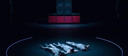 auszug aus einer performance: 3 menschen liefen auf dem boden innerhalb eines kreises. im hintergund eine große lautsprecheranlage