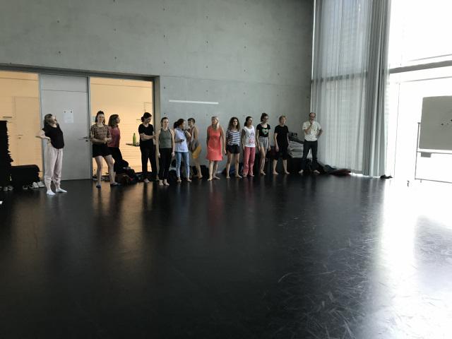 EIne Gruppe Menschen in einem großen Tanzstudio