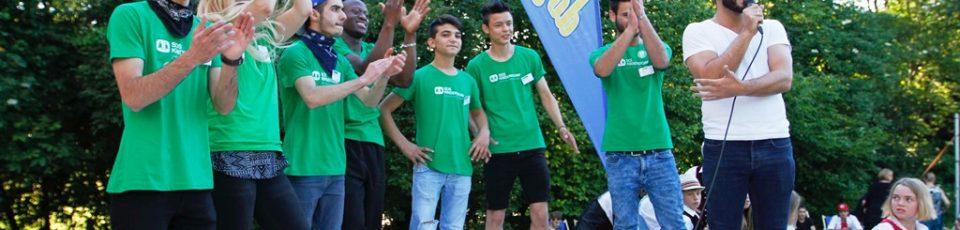 Onur Bakis mit einer Gruppe Jugendlicher auf einer Bühne