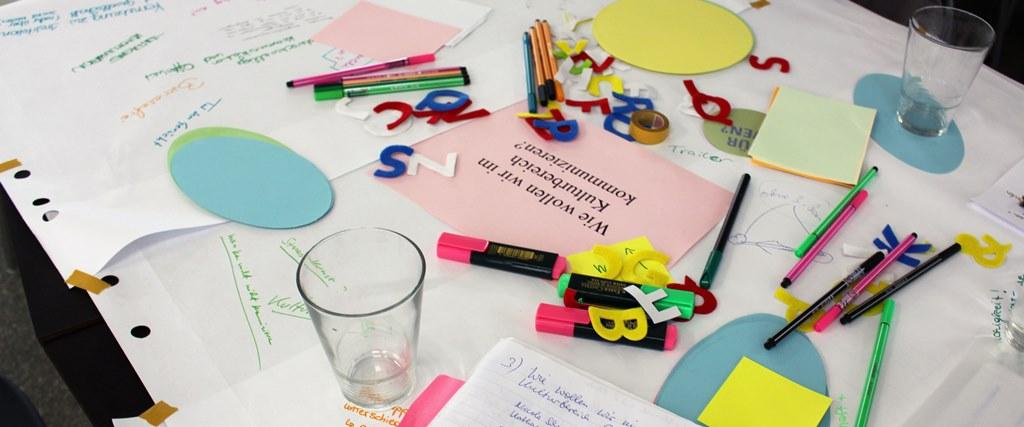 ein tisch mit weißem paper bedeckt, darauf post its und stifte und die frage wie wollen wir im kulturbereich kommunizieren