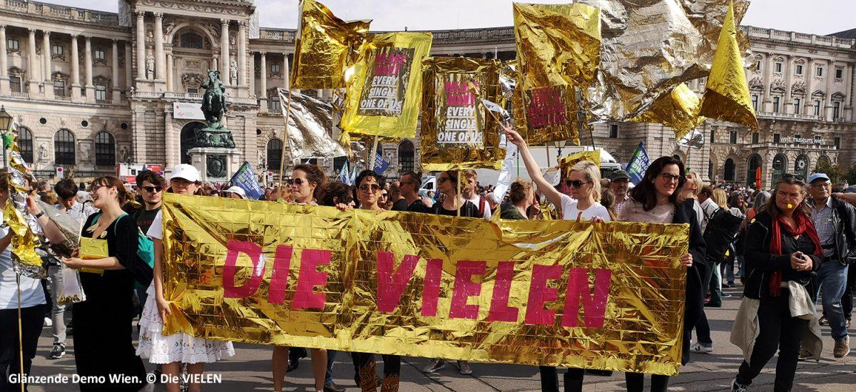 glänzende demo wien mit vielen menschen und goldenem die vielen-transparent