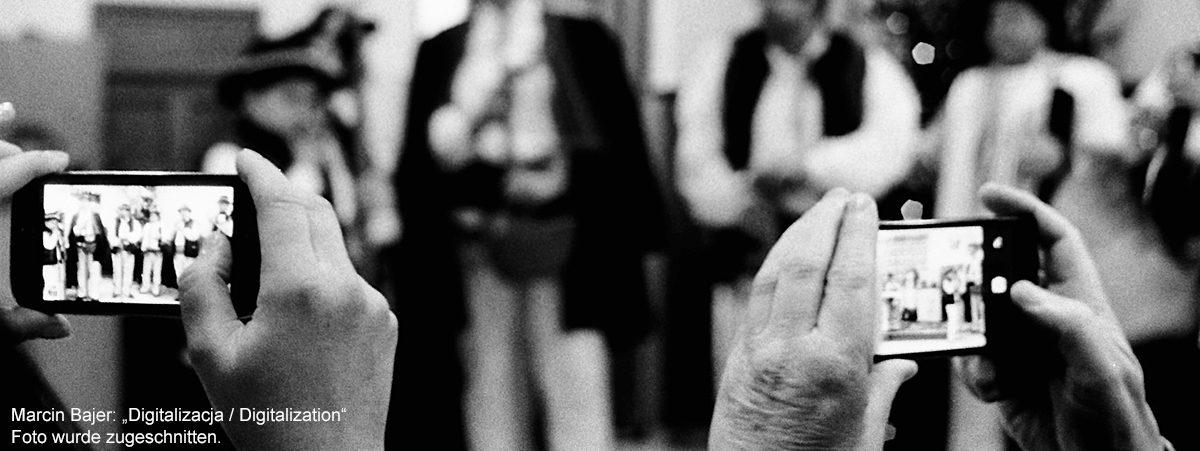 Hände, die gerade mit Smartphones fotografieren. Hintergrund verschwommene Mensche. Copyright Marcin Bajer