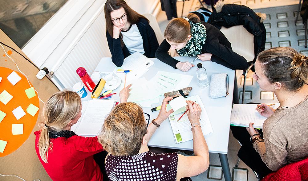 vier frauen sitzen rund um einen tisch und diskutieren