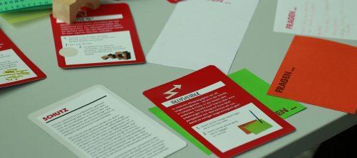 karten mit verschiedenen beschriftungen liegen auf einem tisch, z.b. ideenspender, schutz, fragen