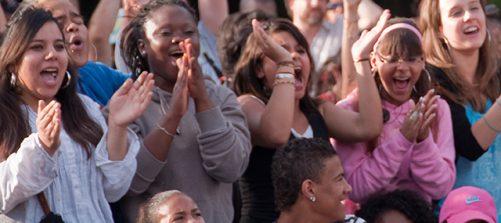 eine gruppe junger menschen jubelt und klatscht in die hände