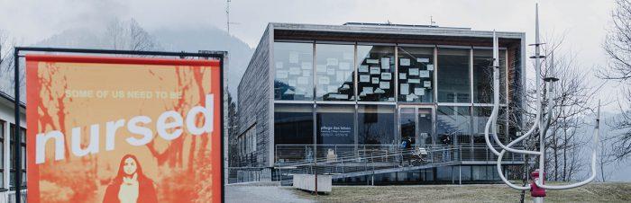 Außenansicht des Frauenmuseums hittisau. links im bild ein plakat mit der aufschrift some of us need to be nursed