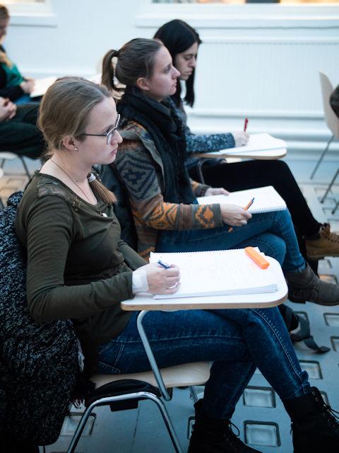 Drei Studeninnen sitzen auf Sesseln und schreiben