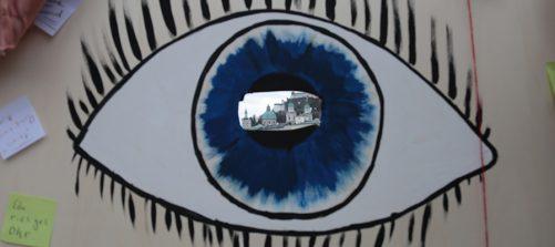 ein Auge auf karton gemalt, in der mitte ein loch, durch das man die festung hohensalzburg sieht