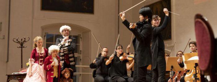 ein orchester mit dirigentin elisabeth fuchs, außerdem personen mit kostüme aus mozarts zeit