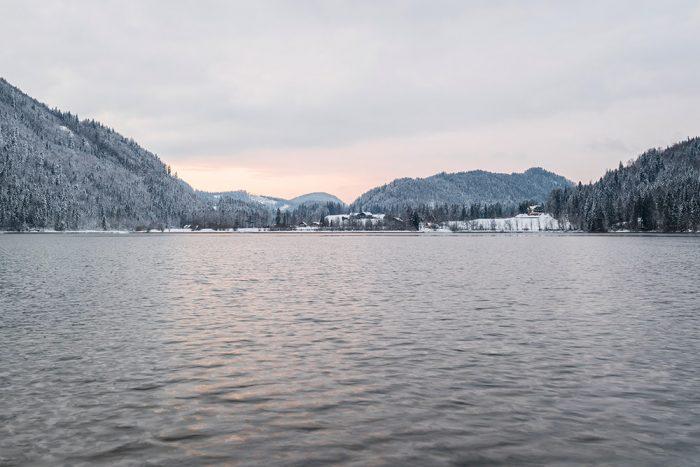das bild zeigt den Hntersee im Winter, im Hintergrund beschneite Hügel
