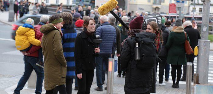 eine Person wird von zwei jungen Frauen mit Mikro und Kamera interviewt