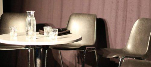 drei sessel um einen runden tisch, darauf wasserkrug und gläser