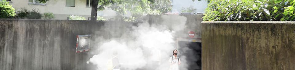 vor einer tiefgaragenausfahrt stehen menschen im rauch